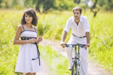 Couple man and woman in wedding style with bikes in nature happy